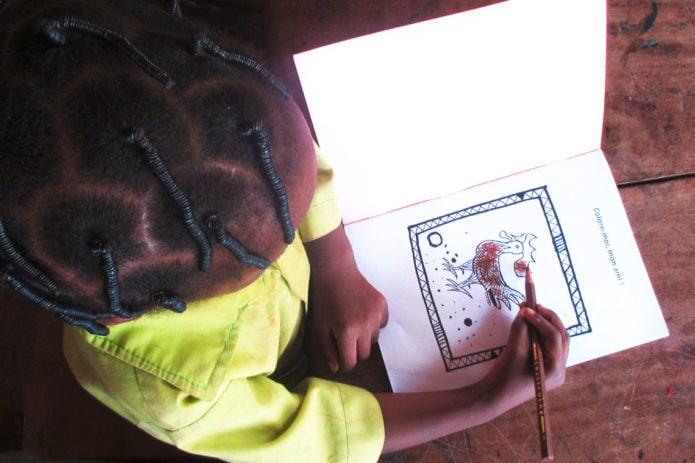 Eine junge Ayeke-Schülerin malt in einem von der Stiftung Hilfe zur Selbsthilfe in Tobe/Benin produzierten Malbuch